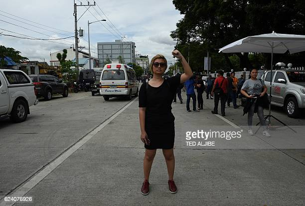 A lone antiMarcos protestor raises clinch fist during a protest in front of the gates of the heroes' cemetery while the late dictator Ferdinand...