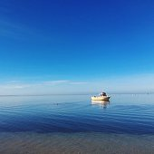 Lone Boat In Calm Blue Sea Against Sky