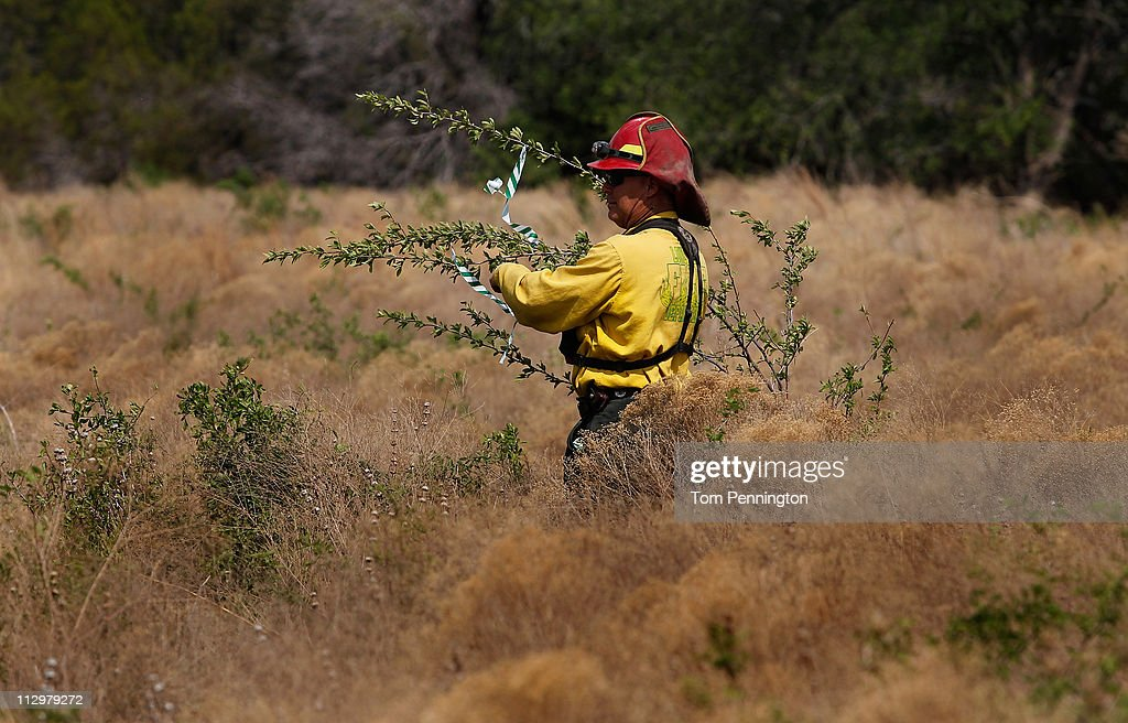Lone Camp assistant fire chief Brandon Thornburg uses flagging tape while surveying the construction of a 66-foot wide fire containment line on April 22, 2011 in Strawn, Texas. Fire crews are using heavy machinery to help contain the PK Complex Fire that has destroyed more than 160 homes in the area.