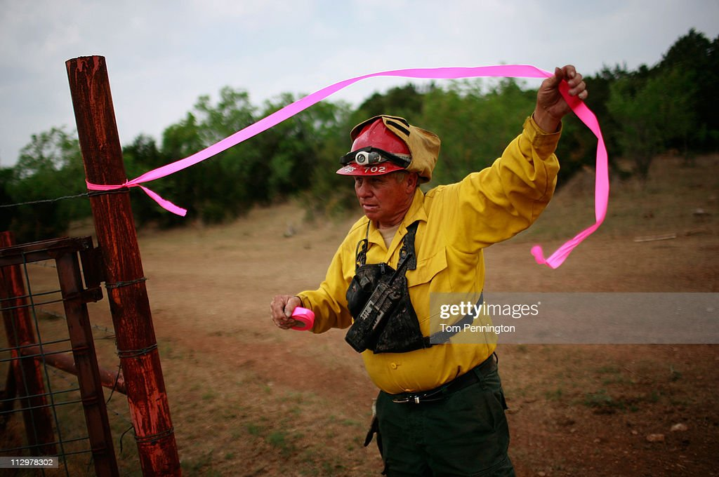 Lone Camp fire chief Charlie Sims uses pink flagging tape while surveying the construction of a 66-foot wide fire containment line on April 22, 2011 in Strawn, Texas. Fire crews are using heavy machinery to help contain the PK Complex Fire that has destroyed more than 160 homes in the area.