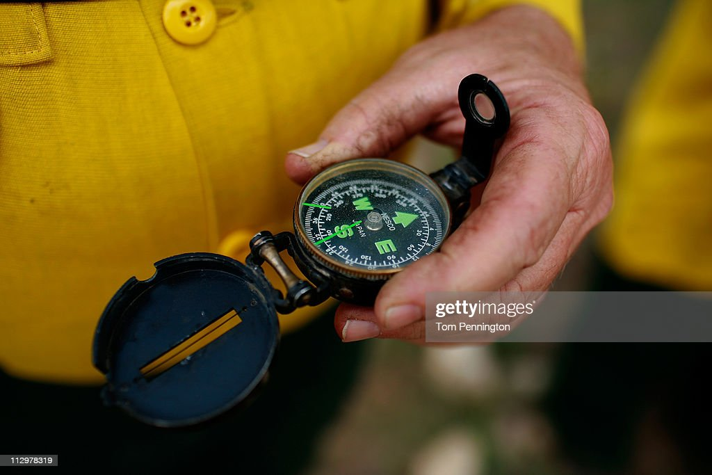 A Lone Camp fireman uses a compass to confirm the wind direction on April 22, 2011 in Strawn, Texas. Fire crews are using heavy machinery to help contain the PK Complex Fire that has destroyed more than 160 homes in the area.