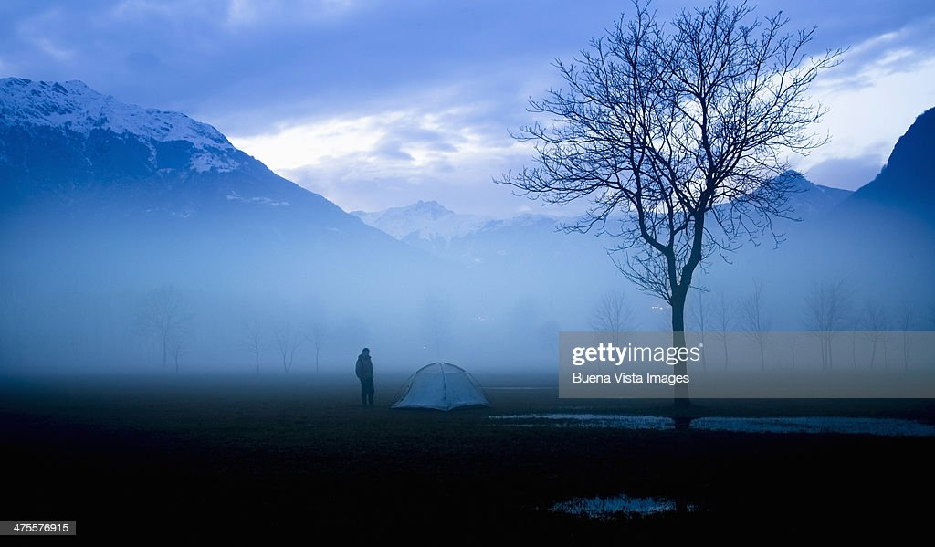 lone camper close to tent at night : Stock Photo