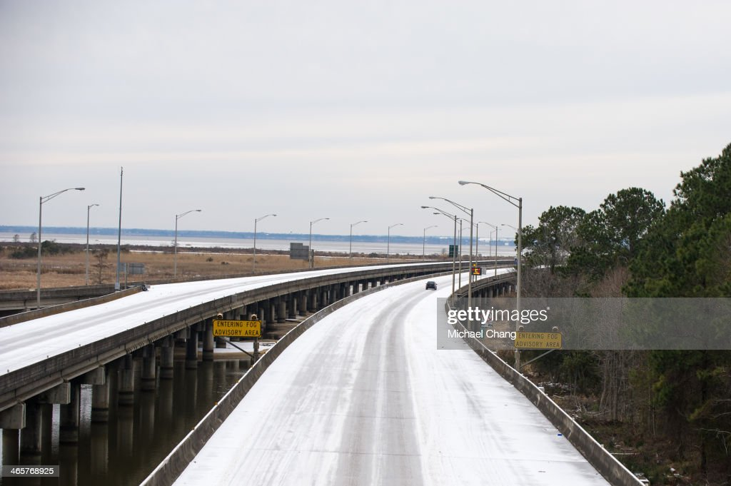A lone car drives along Interstate 10 West bound on January 29, 2014 in Daphne, Alabama. A rare winter storm has brought ice and snow across the southern states closing schools and stranding motorists.