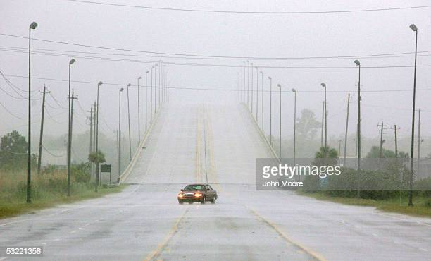 A lone car drives through the rains from Hurricane Dennis July 10 2005 in Mobile Alabama Dennis made landfall with 120 mph winds on Santa Rosa Island...