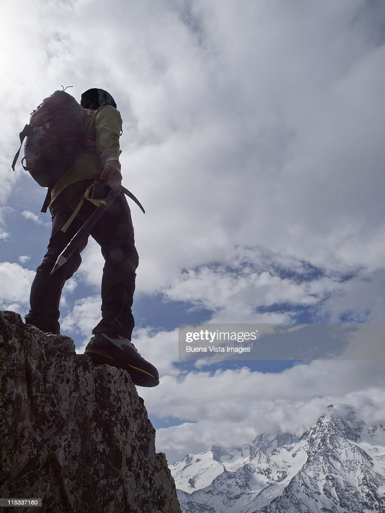 Lone climber on top of a peak : Stock Photo