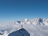 Lone climber on top of a snowy peak