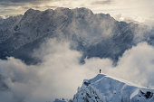Lone climber standing on a snowy peak