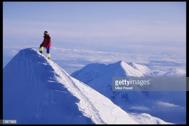 A lone climber stands on the Summit Ridge at Denali on Mount McKinley Alaska