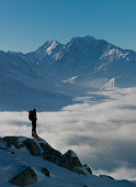 Lone climber watching a mountain over a fog sea