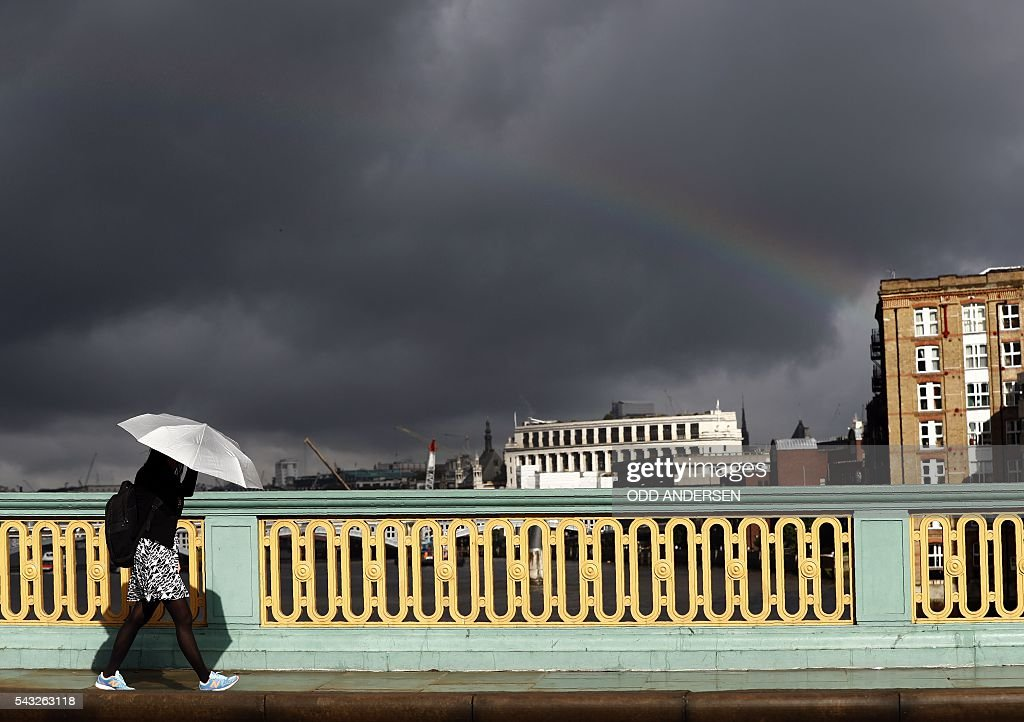A lone commuter shelters from the rain beneath her umbrella as she walks beneath a rainbow into the City of London across Southwark Bridge in central London on June 27, 2016. Britain should only trigger Article 50 to leave the EU when it has a 'clear view' of how its future in the bloc looks, finance minister George Osborne said Monday following last week's shock referendum. London stocks sank more than 0.8 percent in opening deals on Monday, despite attempts by finance minister George Osborne to calm jitters after last week's shock Brexit vote. / AFP / ODD