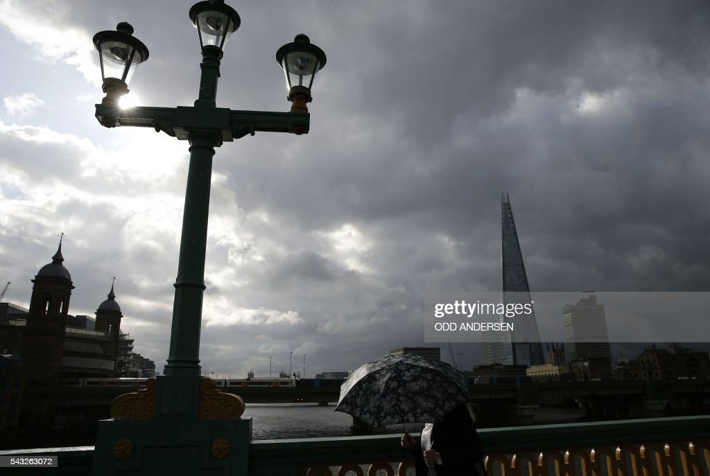 A lone commuter shelters from the rain beneath her umbrella as she heads into the City of London across Southwark Bridge in front of the Shard skyscraper in central London on June 27, 2016. Britain should only trigger Article 50 to leave the EU when it has a 'clear view' of how its future in the bloc looks, finance minister George Osborne said Monday following last week's shock referendum. London stocks sank more than 0.8 percent in opening deals on Monday, despite attempts by finance minister George Osborne to calm jitters after last week's shock Brexit vote. / AFP / ODD