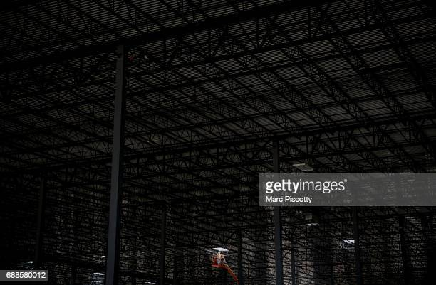 A lone construction worker on a lift works on sprinkler fittings at a new Amazon Fulfillment Center on April 14 2016 in Aurora Colorado The...