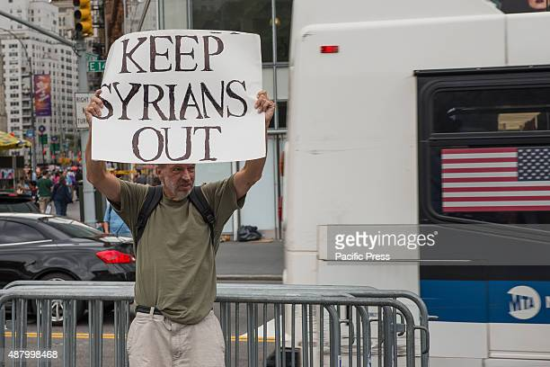 A lone counter protester James MacDonald stands on the curb declaring the opposite of the rally's message Mr MacDonald objects the proposed US asylum...