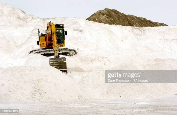 A lone digger prepares low grade salt for wagons to collect from British Salt in Middlewich Cheshire as more snow is expected later today in some...