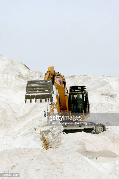 CROP A lone digger prepares low grade salt for wagons to collect from British Salt in Middlewich Cheshire as more snow is expected later today in...