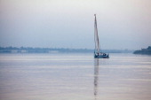 A lone felluca a traditional Egyptian sail boat sails an empty looking Nile River on October 23 2013 in Luxor Egypt Luxor one of Egypt's major...