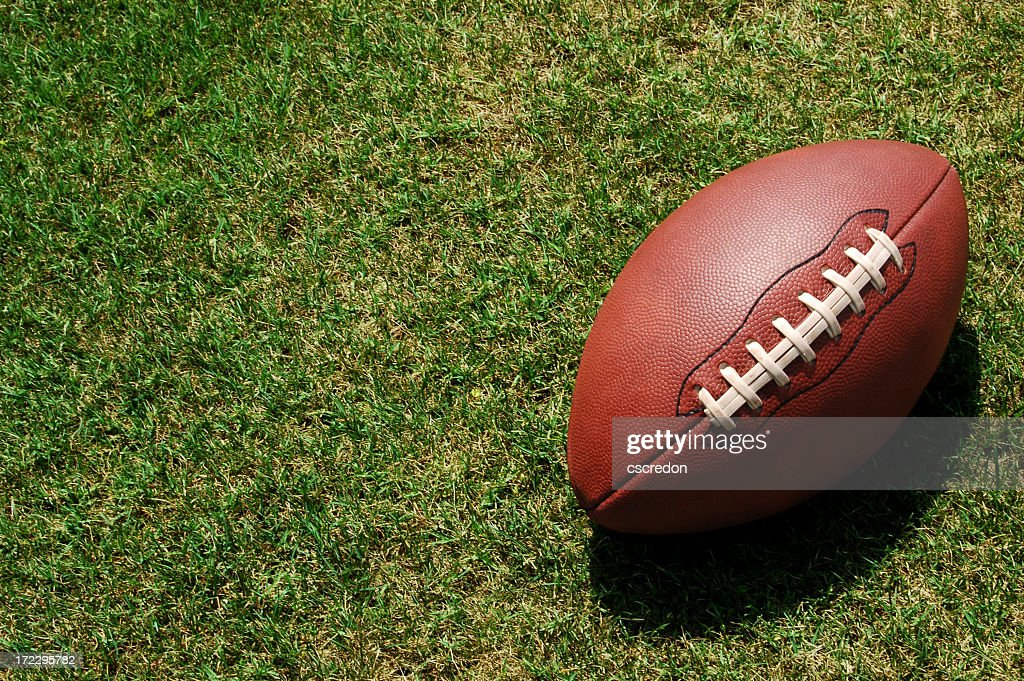 A lone football resting in the green grass