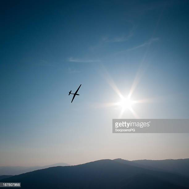 lone glider flies to the sun, mountain panorama and sky