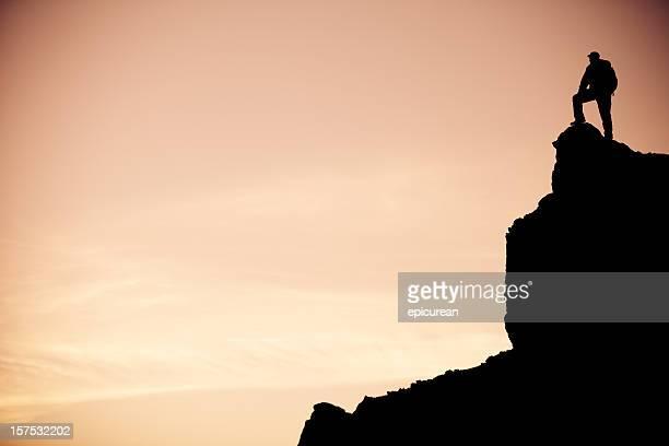 Randonneur solitaire profite de la vue sur le lever du soleil depuis une falaise