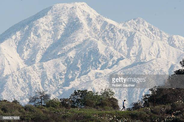 A lone hiker travels along the Summitridge Park Trail in Diamond Bar framed by the snowcapped San Gabriel mountains on a brisk morning after a...