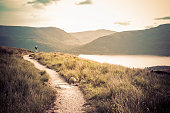 A Caucasian person is hiking through Ben Lomond by Loch Lomond, Scotland.  The person is on a dirt path with long grass on each side.  The sky is pale yellow with a few clouds.  There are dark mountai