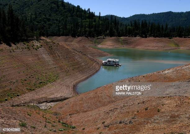 A lone houseboat beside an almost dry section of the Shasta Lake reservoir which is now at less than 20 percent capacity as a severe drought...