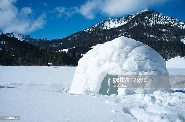 A lone igloo in a mountainous scene