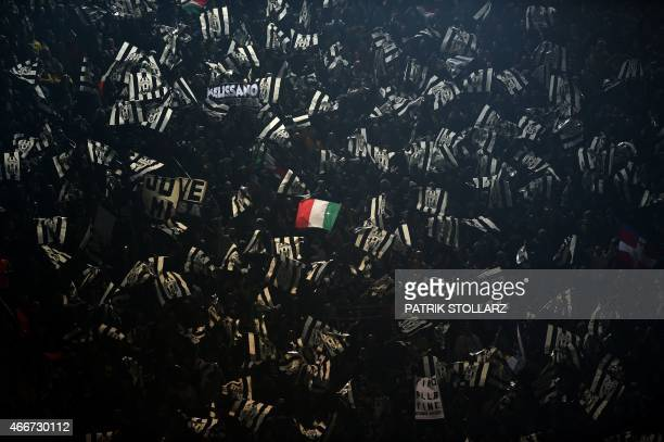 A lone Italian flag is waved amongst a sea of Juventus' flags during the Round of 16 secondleg UEFA Champions League football match Borussia Dortmund...