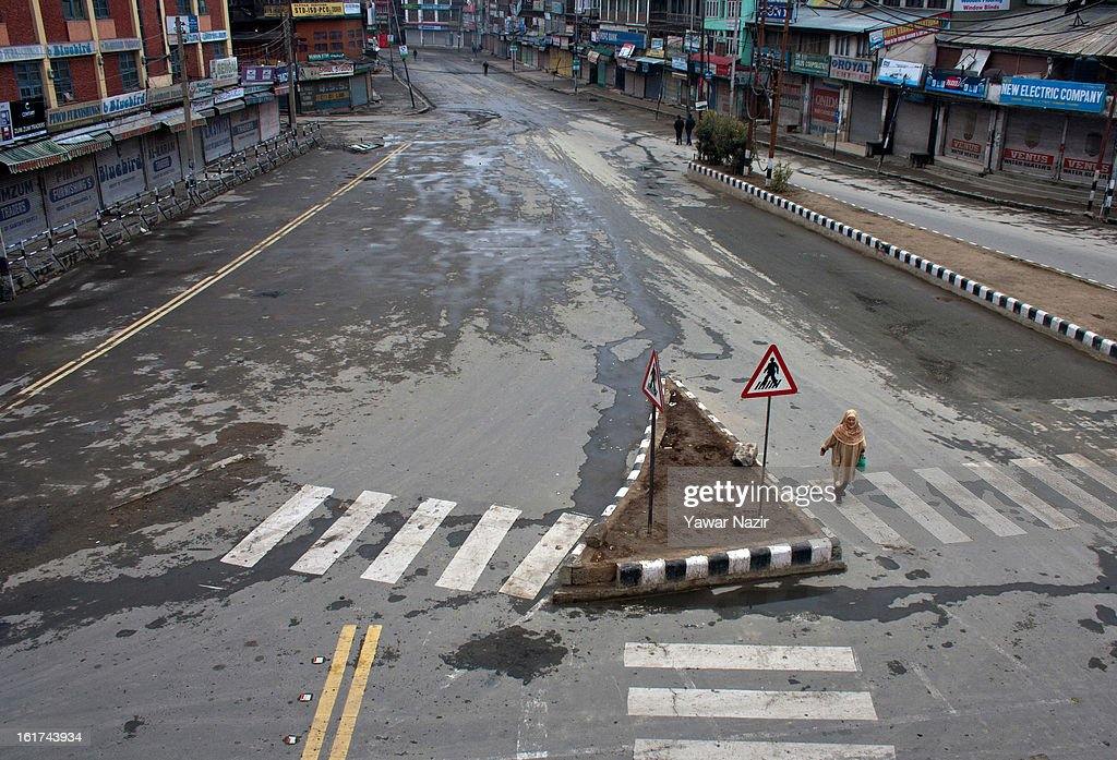 A lone Kashmiri Muslim woman negotiates curfew bound streets during a strict curfew on the seventh consecutive day, imposed after the execution of alleged Indian parliament attacker Mohammad Afzal Guru on February 15, 2013 in Srinagar, the summer capital of Indian Administered Kashmir, India. Afzal Guru, from Sopore town in the north of Kashmir, was hung on February 09 for his role in the 2001 Indian parliament attack which left 14 dead. The hanging has further strained relations between India - who blamed the attack on 'Pakistan backed' militant group Jaish-e-Mohammed - and neighbouring Pakistan and has seen an military increase from both along the border.Curfew was lifted from some parts of Srinagar after four days.