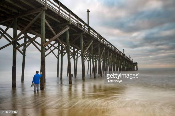 Einsamer Mann am Strand im Wasser vor Pier steht