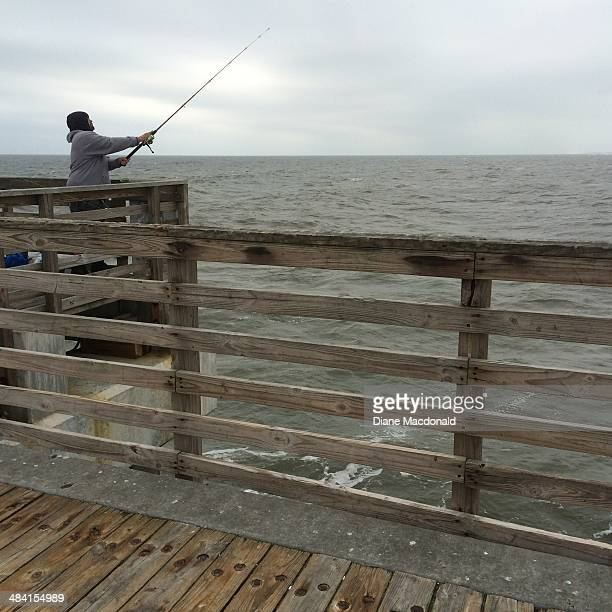 Lone man fishing from Jacksonville Beach Fishing Pier Florida on a stormy day