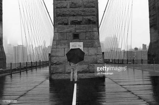 A lone man reads an 'Award of Merit' sign on a rainy Brooklyn Bridge New York City circa 1980