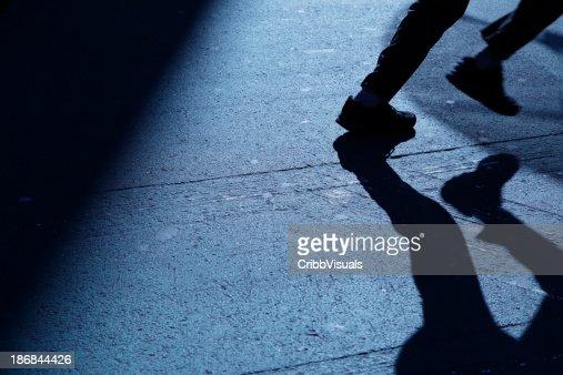 Lone man running away in blue night shadows