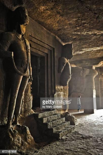 A lone man walks past a shrine in the Elephanta Caves, Mumbai, Maharashtra, India