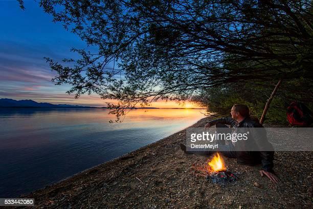 Einsamer Mann mit Lagerfeuer während dem Sonnenuntergang, Chiemsee, bayerische