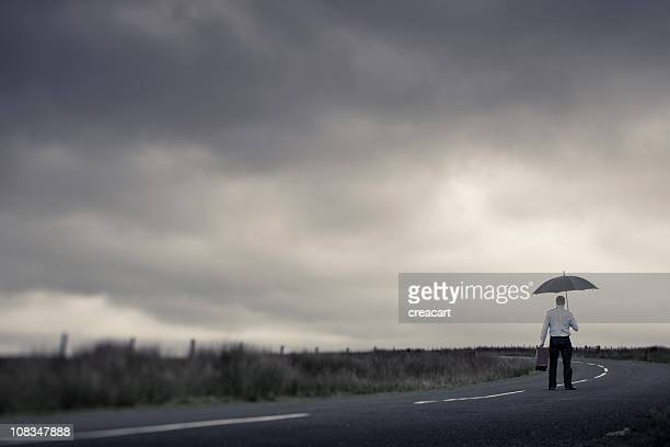 Lone Man with Suitcase and Umbrella on a dark road
