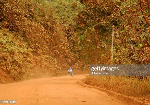 A lone motorcyclist is driving on a dirt road on April 26 2015 near Ho Chi Minh City Vietnam The Central Highlands region is vital for the production...