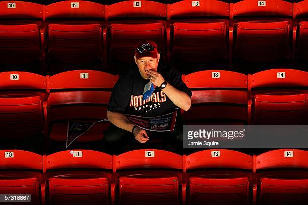 A lone Nationals fan eats peanuts while waiting for the game to begin prior to the Opening Day game between the New York Mets and the Washington...