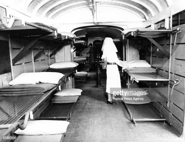 A lone nurse arranges bedding in a deserted carriage of a hospital train in preparation for receiving wounded soldiers