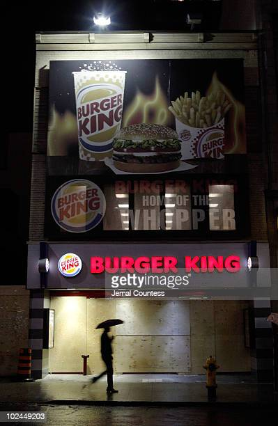 A lone pedestrian walks by a Burger King on Younge St in downtown Toronto that was heavily damaged during demonstrations that occured earlier in the...