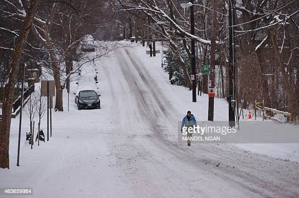 A lone pedestrian walks in the middle of a street avoiding snowcovered sidewalks in the northwest of Washington DC on February 17 2015 Some 10 to 15...
