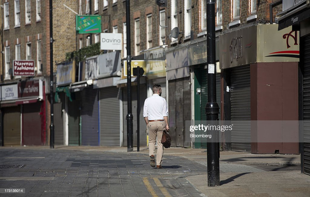 A lone pedestrian walks past a row of shuttered and closed stores in London, U.K., on Monday, July 8, 2013. Britain's economy could be in line for a period of 'strong catch-up growth' once it gets through the current weakness, according to Capital Economics Ltd. Photographer: Simon Dawson/Bloomberg via Getty Images