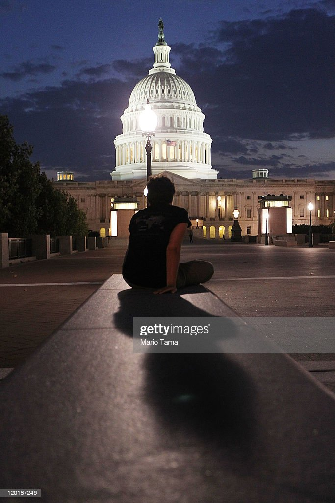 A lone person looks on towards the U.S. Capitol building on July 31, 2011 in Washington, DC. U.S. President Barack Obama announced that congressional leaders had reached an agreement to extend the federal debt limit while enacting spending cuts.