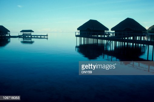 Lone Person Standing on Pier in Tropical Resort