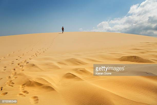 Lone person walking up a big sand dune
