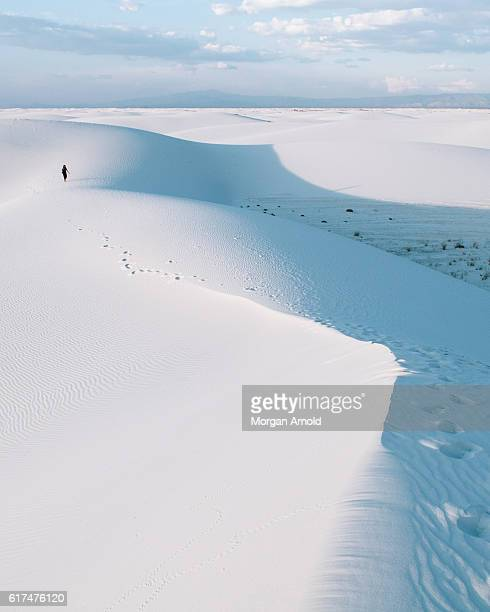 A lone person walks on sand dunes in the distance in White Sands National Monument