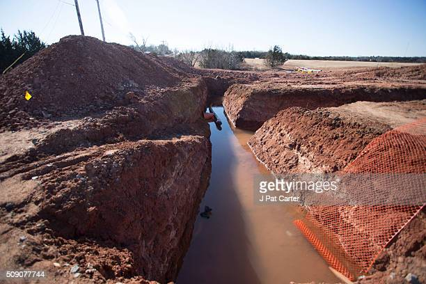 A lone pipe sits in a man made ditch that will carry a pipe line to a fracking oil well site January 27 2016 near Stillwater Oklahoma