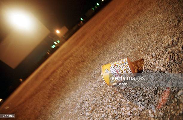 A lone popcorn bucket lays on the ground after a night at the movies August 10 2000 at the Fiesta drivein theater in Carlsbad New Mexico In the 1960s...