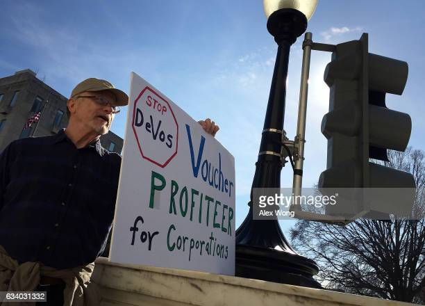 Lone protester Charlie Zellers of Wheaton Maryland holds an antiDeVos sign outside Russell Senate Office Building on Capitol Hill February 6 2017 in...