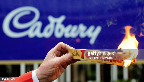 A lone protestor burns a Toblerone chocolate bar packet outside the Bournville factory Birmingham after it was announced that Cadbury had backed a...